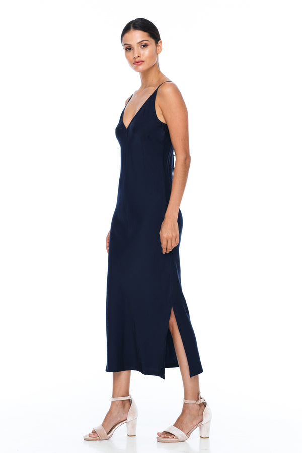 The Cairo Dress is part of the BLAK BRIDESMAIDS - Made to Order Collection.  Featuring a low v neckline and adjustable thin straps with tie detail in back. A classy chic fitted dress cut on the bias for a slinky fit.  - Midi Length  - Side Splits - Navy - Side Front View
