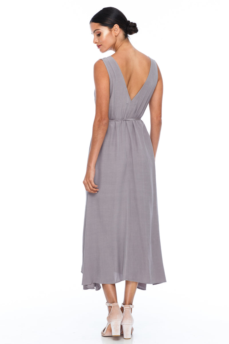 BLAK BRIDESMAIDS -  Calm Dress - Pewter - Featuring a low v-neckline front and back with wider straps. An easy fit dress with self-waist tie.  Midi Length / 100% viscose. Image shows back view