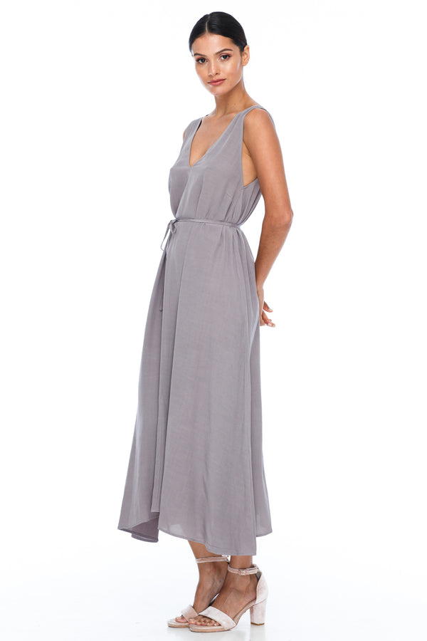 BLAK BRIDESMAIDS -  Calm Dress - Pewter - Featuring a low v-neckline front and back with wider straps. An easy fit dress with self-waist tie.  Midi Length / 100% viscose. Image Shows side view