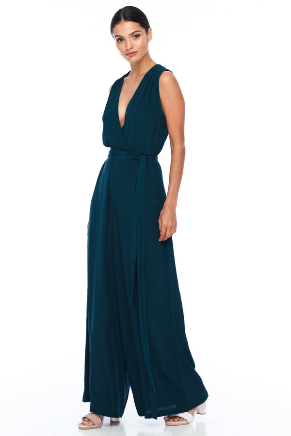 A BLAK Bridesmaid Piece - The Keep Me Jumpsuit features a beautifully low v-neck front and back, with gathered body into a wide leg. Also comes with a sash belt to bring in at waistline - Emerald - Side View
