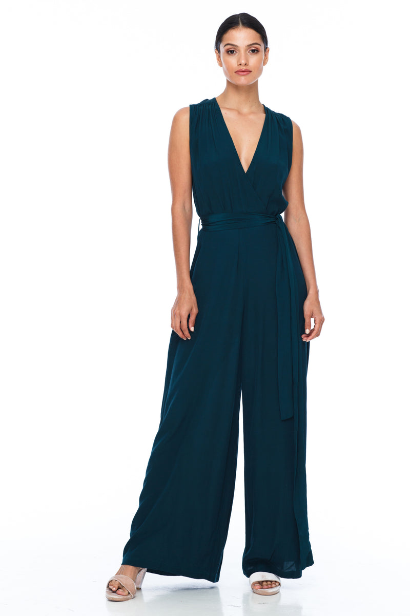 A BLAK Bridesmaid Piece - The Keep Me Jumpsuit features a beautifully low v-neck front and back, with gathered body into a wide leg. Also comes with a sash belt to bring in at waistline - Emerad - Front View