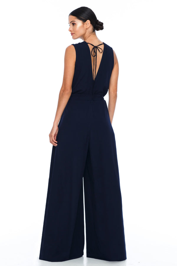 A BLAK Bridesmaid Piece - The Keep Me Jumpsuit features a beautifully low v-neck front and back, with gathered body into a wide leg. Also comes with a sash belt to bring in at waistline - Navy - Front View