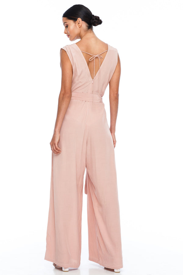 A BLAK Bridesmaid Piece - The Keep Me Jumpsuit features a beautifully low v-neck front and back, with gathered body into a wide leg. Also comes with a sash belt to bring in at waistline - Rose - back View