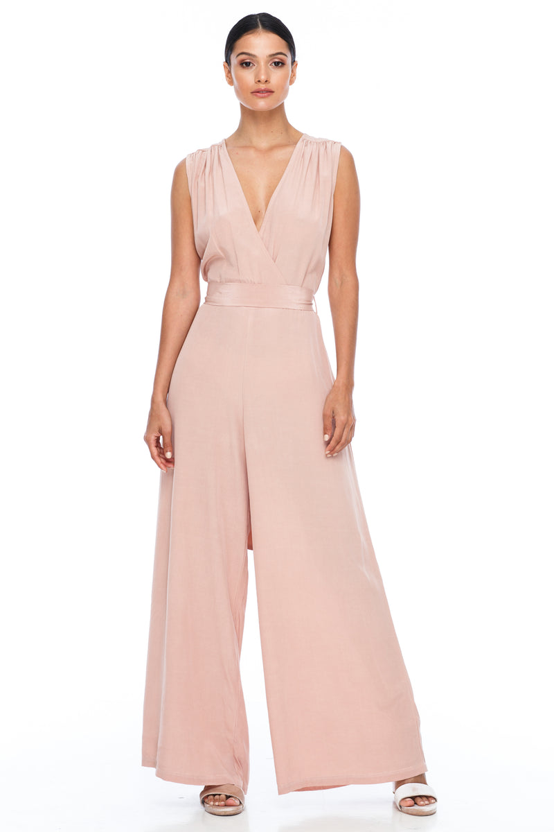 A BLAK Bridesmaid Piece - The Keep Me Jumpsuit features a beautifully low v-neck front and back, with gathered body into a wide leg. Also comes with a sash belt to bring in at waistline - Rose - Front View