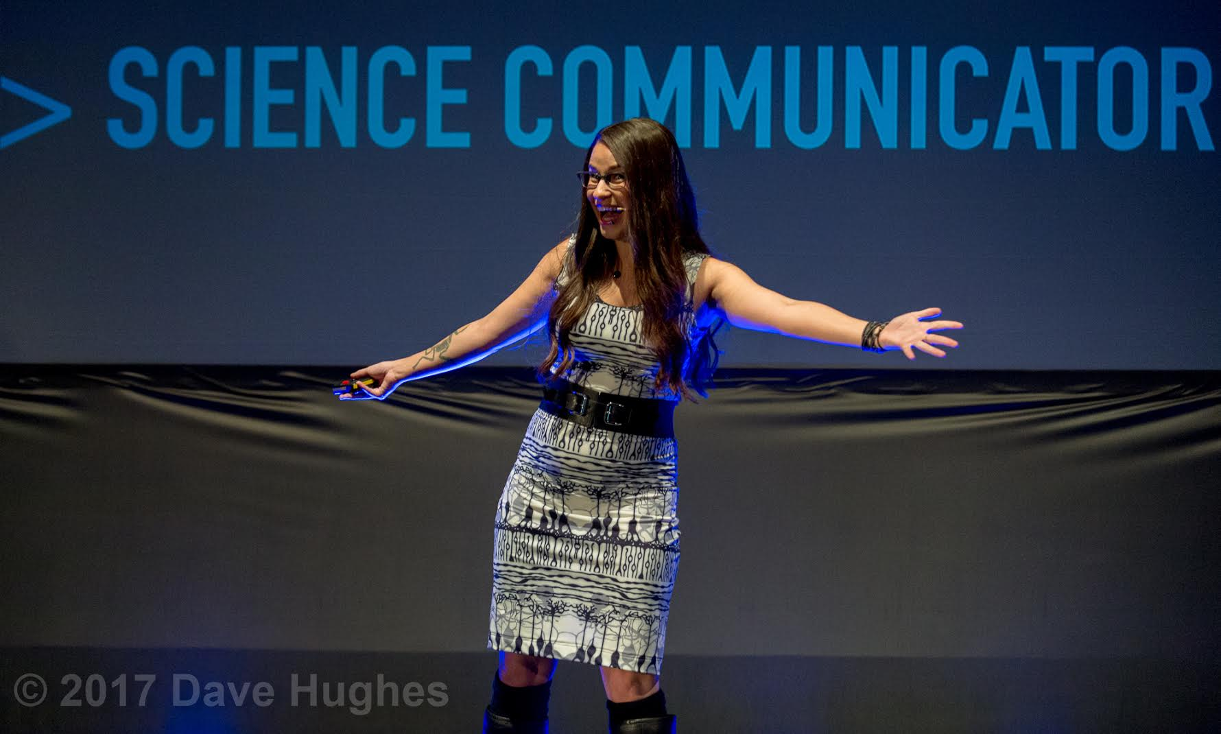 Cara Santa Maria Science Communicator on stage in Neuroscience Shenova Dress