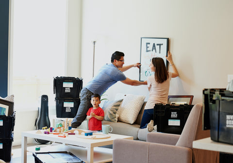 Couple hanging a print on wall