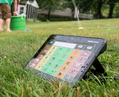 Angled view of the Tobii Dynavox I-110 SGD outdoors in grass featuring the Snap Core First AAC app