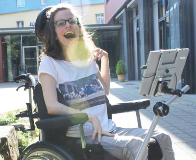Young woman using her Tobii Dynavox EyeMobile Mini Bracket outside