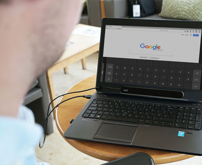 Man using a Tobii Dynavox eye tracker on his laptop at home