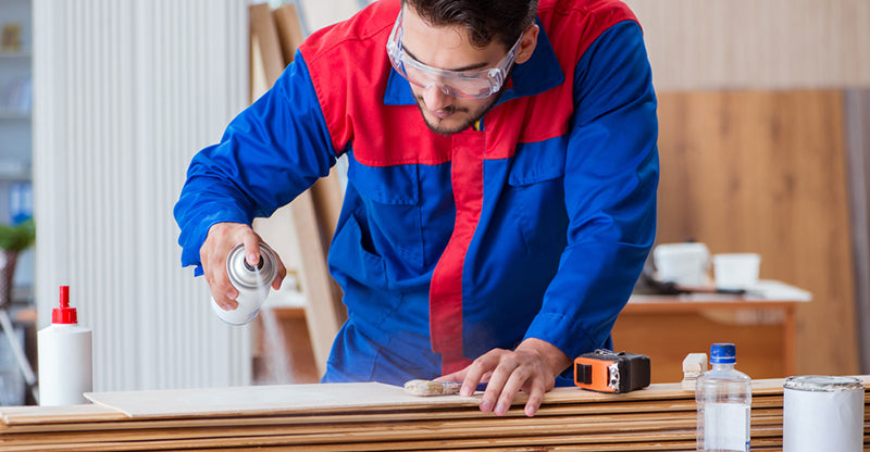 man using spray adhesive wood