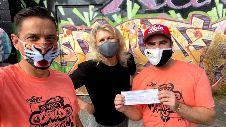Robert Pacey and Stacy Hall of MAKE Vancouver present Lucas Riedl, of UNYA, with a cheque in the amount of $37,373.00