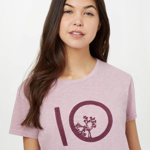 Young woman with long brown hair wearing a pink and purple tentree shirt