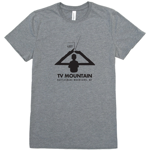 Image of a boy looking at a mountain as if it is a television to represent TV Mountain in Missoula, MT on a gray t-shirt.