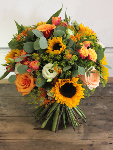 Sunny Day - Bright roses and sunflowers accompanied by warm, textural summer blooms and fresh foliages.
