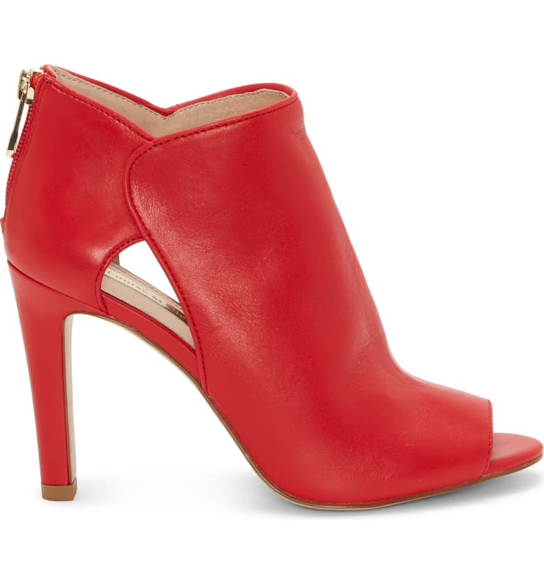 A Louise et Cie, lipstick red, open-toe bootie, mid stiletto heel with side cut outs to amplify the modern appeal. At Shoe Be Do in New Orleans,la.
