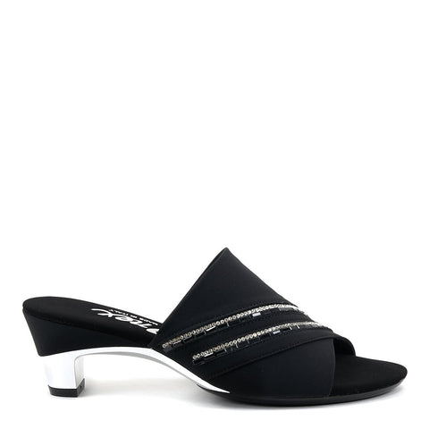 An elegant easy slip-on black low black mule with striking white crystal and black stone ornamentation, finished off with a metallic silver heel. At Shoe Be Do in New Orleans,la.