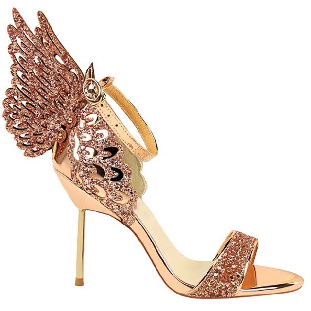A rose gold metallic stiletto, featuring rose gold 3D cut out butterfly wings attached to the back stay. The same pattern embellishes down the back of the heel.  Equipped with an ankle strap and a single toe strap. The open nature of the shoes keeps your feet comfortable even when it is hot out. At Shoe Be Do in New Orleans,la.