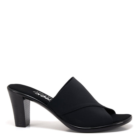 A fashionable, clean, easy slip-on mid height black mule with a elastic fabric upper and a black heel. At Shoe Be Do in New Orleans,la.