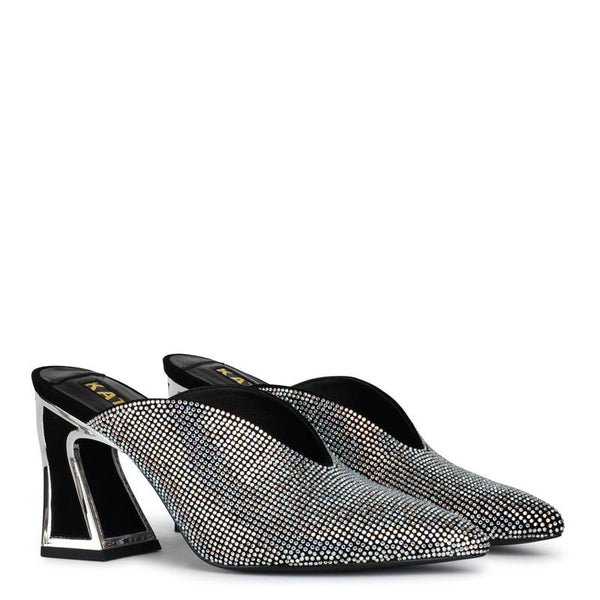 A Kat Maconie mid heel, closed-toe, mule. Entirely embellished with silver-toned crystals, a black signature slanted block heel outlined in mirror silver at Shoe Be Do in New Orleans,la.