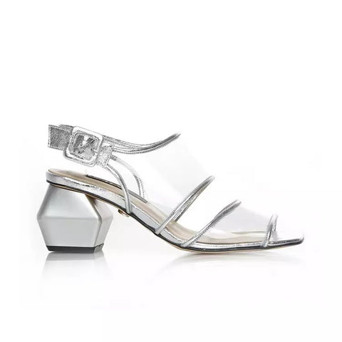 The future is transparent in the custom made Shoe Be Do sandals, featuring a matte silver metallic geometric heel and a clear upper outlined in silver trim with a, adjustable strap and silver buckle.