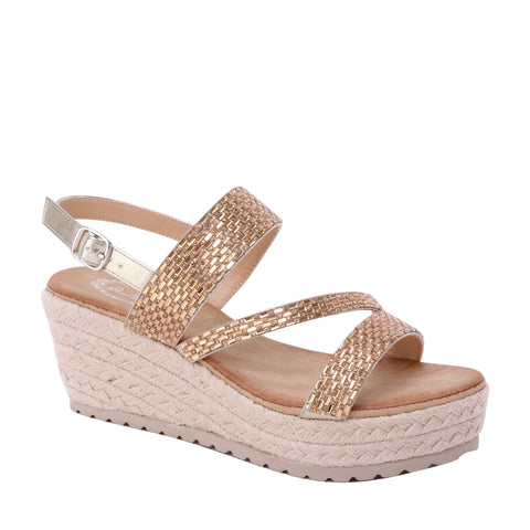 A platform sandal with a wedge heel doused in a gorgeous champagne color. It has ankle strap with an adjustable buckle and a Z-strapped design over the foot. At Shoe Be Do in New Orleans, la.