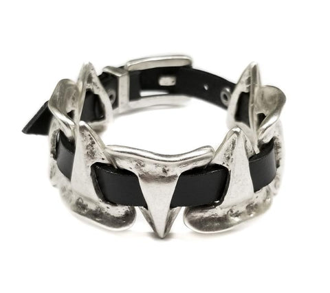 A unisex bracelet, handmade and crafted out of Pewter and genuine leather. Featuring a unique geometric design resembling teeth, heavily connected and inspired by spirituality and ancient relics.  Nickel free and hypoallergenic. In New Orleans,la at Shoe Be Do.