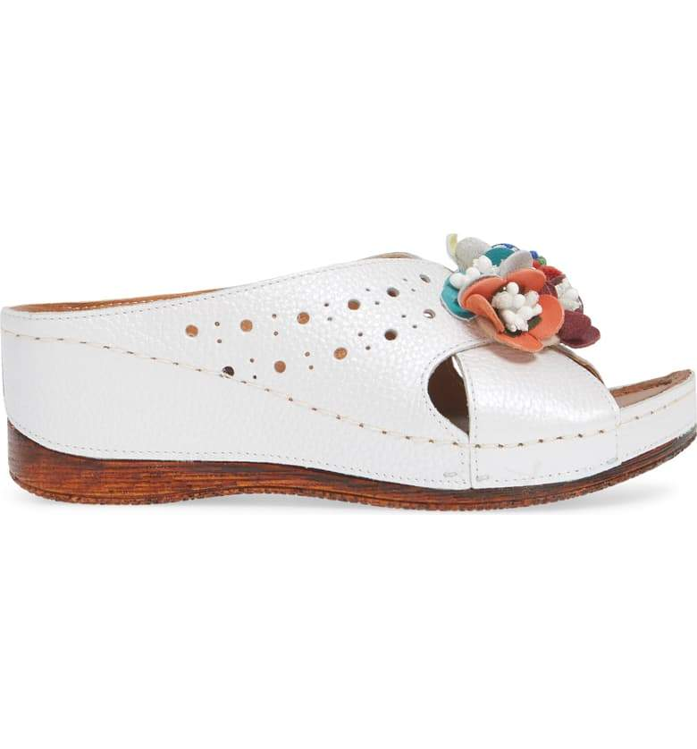 Colorful flowers accentuate the perforated leather straps of a wedge sandal set on a lightly cushioned foot bed. In New Orleans at Nola Foot Candy.