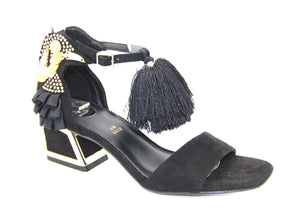 FUN IN THE TROPICS! A low sandal with a block heel outlined in gold, embellished with rhinestones and ruffles resembling a toucan, adorned with a black pom poms.  In New Orleans at Shoe Be Do.