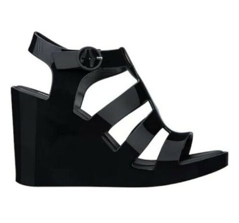 Our new strappy wedge from Melissa features a buckle adjustable strap in a black, resembling patent leather giving it a modern, feminine edge. In New Orleans at Shoe Be Do.