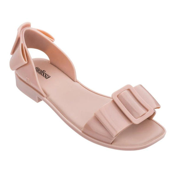 A Melissa, a light pink sandal with a feminine bow and a large buckle. Made completely out of 100% recyclable plastic(PVC) and scented with bubblegum. Will never lose shape or smell and will not make your feet sweat.. at Shoe Be Do in New Orleans,la.