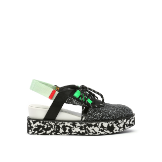 A platform sandal-sneaker hybrid with a United Nude signature design, Miku Sport. It has an open back secured by a mint, tipped in red, slingback. Its an black and white lace-up upper with accents of lime green and black and white sole. In New Orleans at Shoe Be Do.