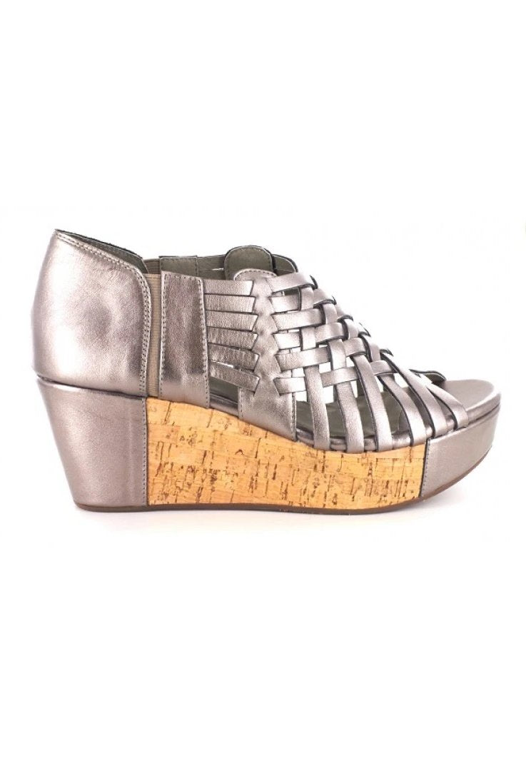 A super comfortable platform wedge sandal in the color gunmetal, made completely out of genuine leather and cork. Featuring intricate web detailing. At Shoe Be Do in New Orleans,la
