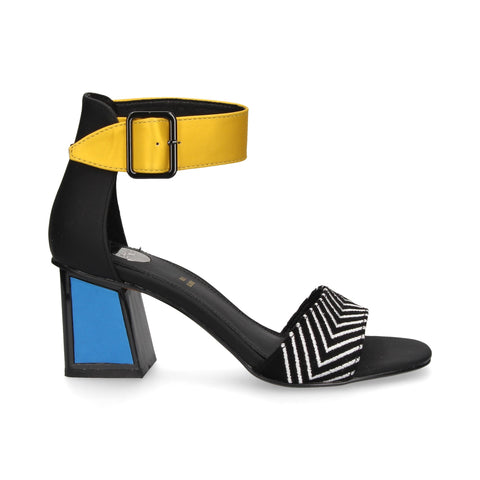 The Exe sandal features a blue geometric mid height block heel with a rubber sole. The model is cut in color blocking fabric and decorated with a yellow adjustable strap around the ankle and a strap over the foot with black and white colored arrow stripes.  Heel Height: 7 cm. At Shoe Be Do in New Orleans,la.
