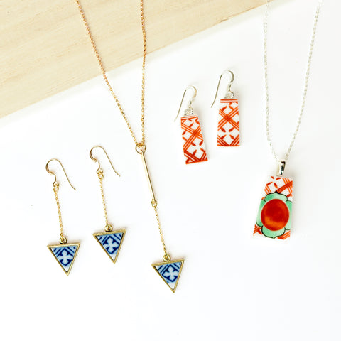 matching set of necklace and earrings made from broken pottery on a tan-colored board
