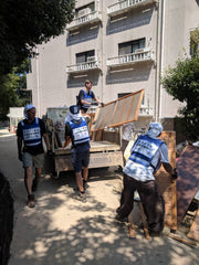 volunteers in blue vests load debris on truck