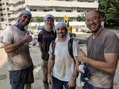 four men are dirty from mudouts but smile at camera