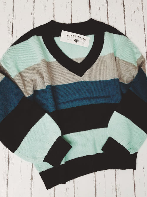 4 colors stripe long sleeve sweater (light blue, grey, black, and dark blue) with a V Neckline and knit details.