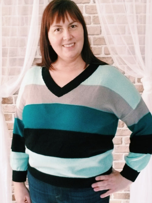 Cozy as a hug, soft drop shoulder vee neck sweater is color blocked in shades of teal, mint, and taupe edged in black.