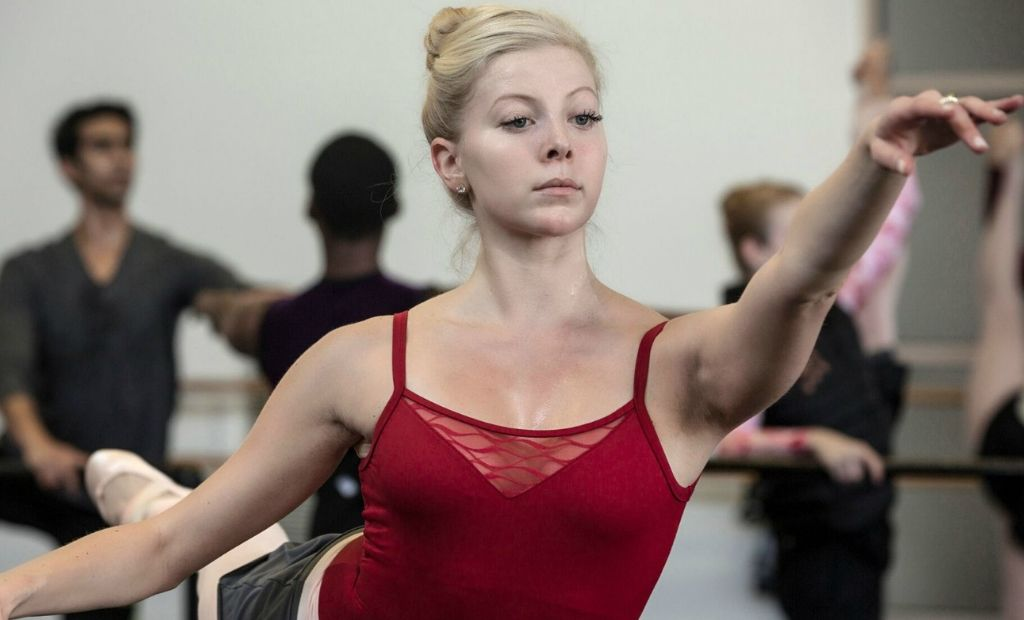 A female ballet dancer wearing a red camisole leotard practising ballet at the barre in the classroom with help from her teacher