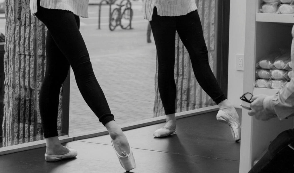 Two dancers pointing their toes at the barre while being fitted for pointe shoes by a BLOCH fitter in a BLOCH store