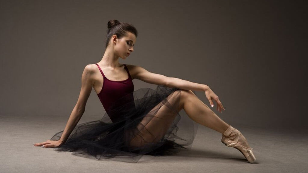 Ballet dancer Maria Khoreva dancing at the barre in blue BLOCH high neckline tank leotard and black tutu