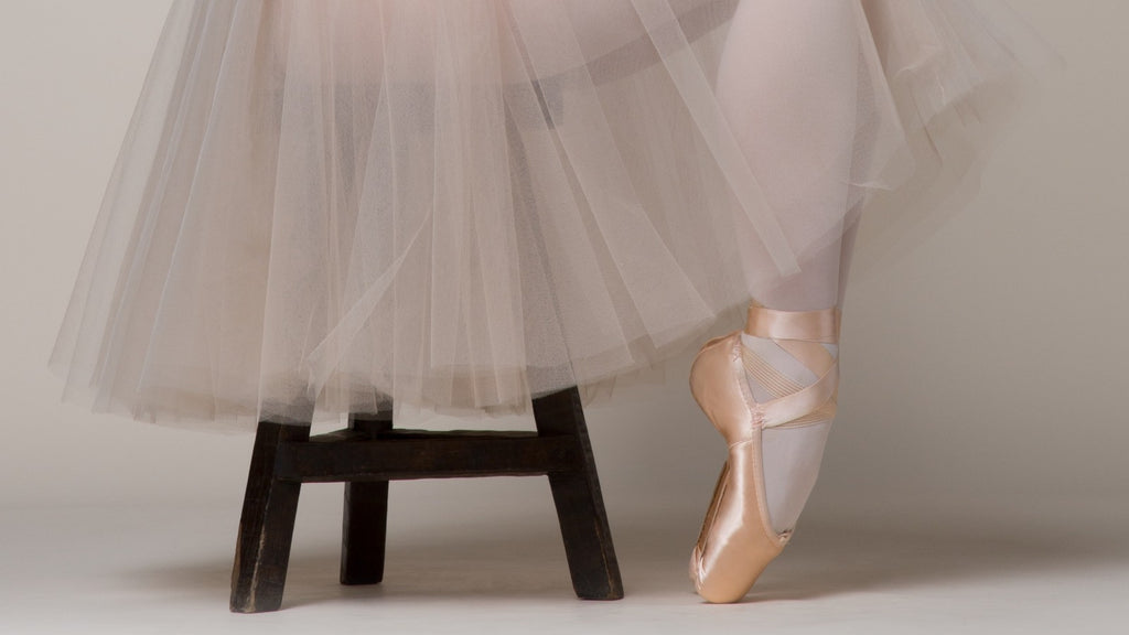 A ballet dancer sitting on a stool with feet in pointe position wearing pointe shoes and a tutu