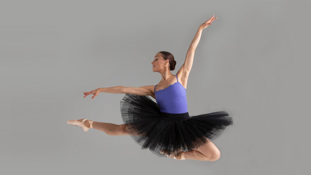 A ballet dancer leaping through the air wearing a BLOCH lilac camisole leotard with black tutu and pointe shoes