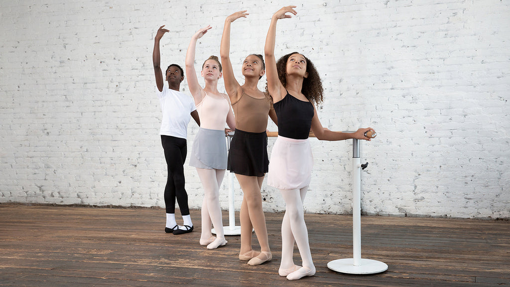 Four young ballet dancers practising at the barre in the classroom
