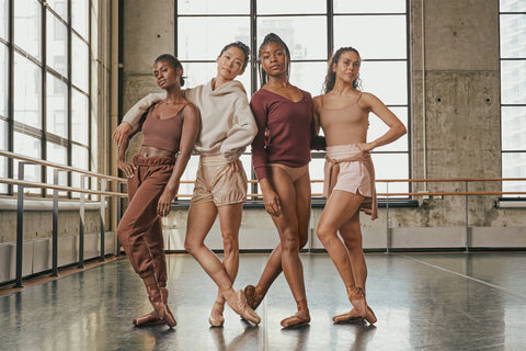 group of dancers wearing pointe shoes that match their skin tone