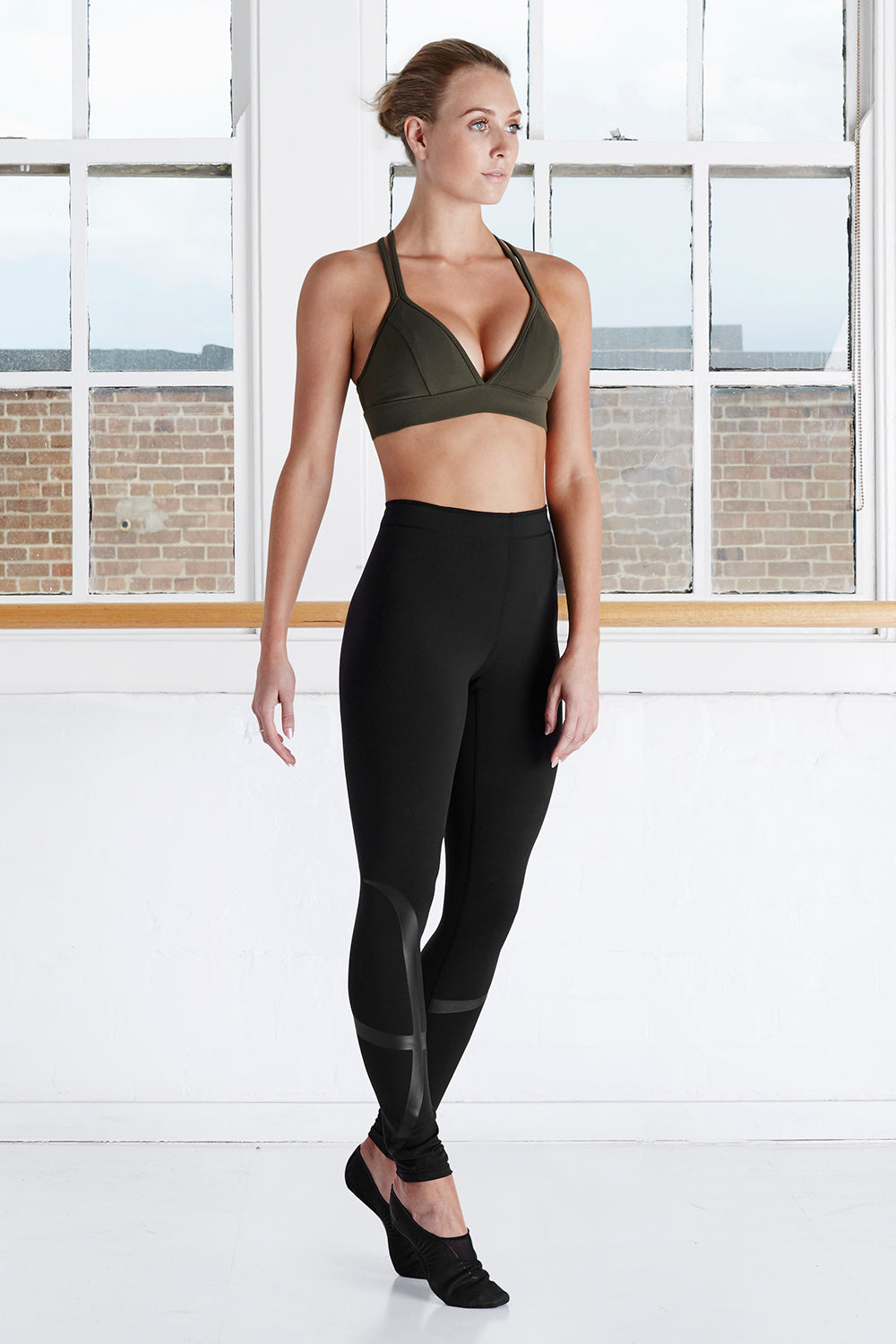 A female dancer in the studio wearing BLOCH active bra top with BLOCH branded stirrup legging