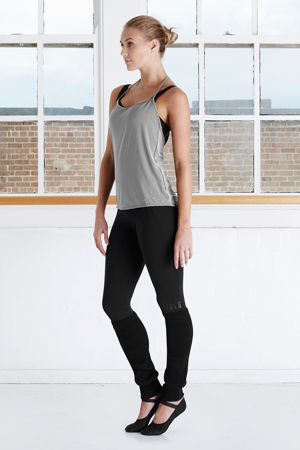 A female dancer in the studio wearing the Ladies BLOCH Branded T Back Top and stirrup leggings