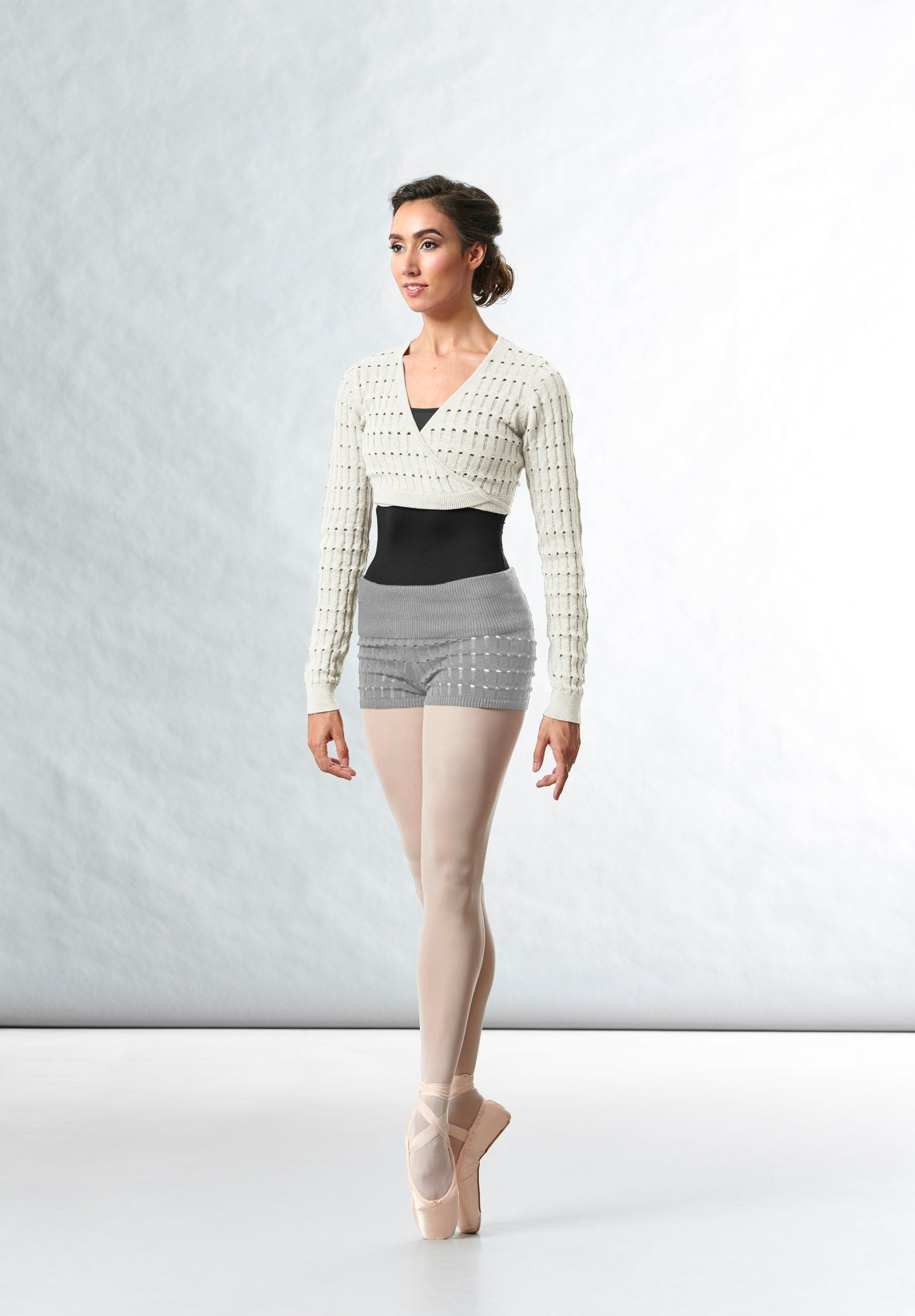 A female ballet dancer wearing a black BLOCH leotard, knitted wrap top and shorts