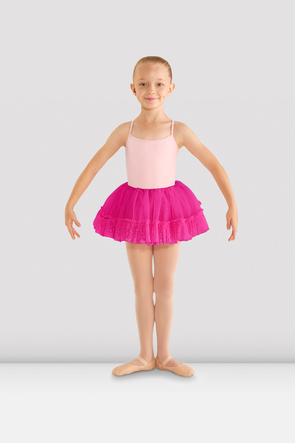 A young female ballet dancer wearing a candy pink camisole leotard with Girls Addelyn heart mesh tutu