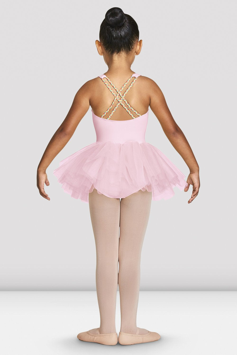 Candy pink Bloch Girls Clara Strap Tank Tutu Leotard on female model feet in first with arms in demi bra facing back
